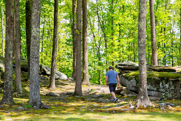 Hiker wanders among rocks near River Expeditions
