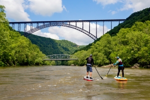 Paddle-boarders navigate toward New River Gorge Bridge