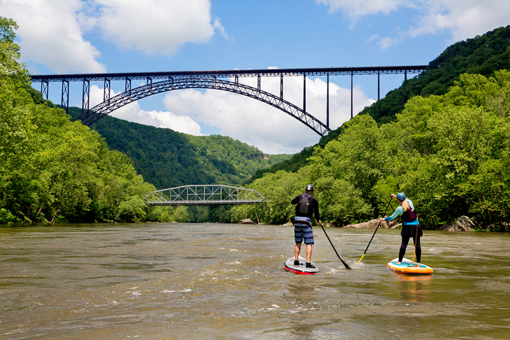 Paddle-boarders angle toward New River Gorge Bridge