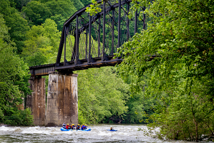 Rafters paddle beneath historic trestle