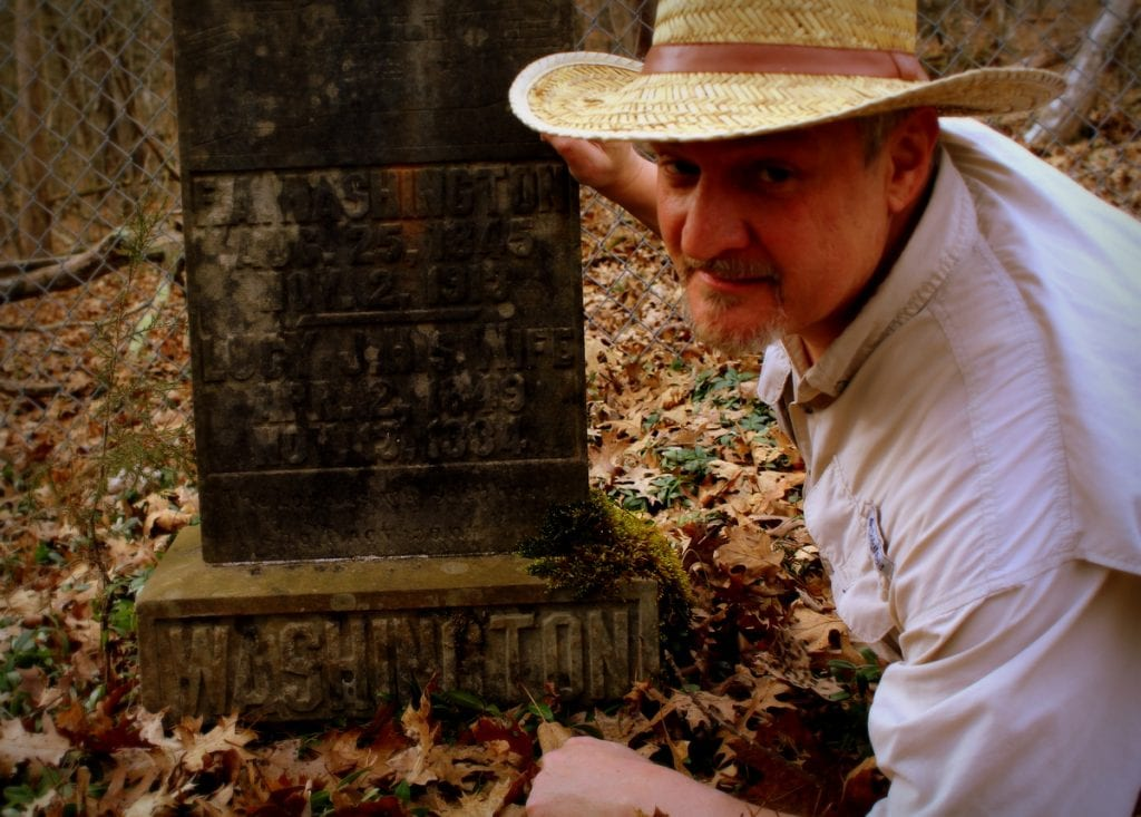 David Sibray examines a Washington family headstone near the mouth of Hurricane Creek in Putnam County, West Virginia.