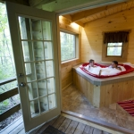 A couple soaks in a vintage hear-shaped tub at Country Road Cabins