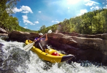 A paddler in an inflatable kayak challenges the Dries of the New River.
