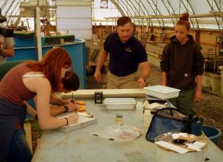 Biologist Brandon Keplinger (center) works with staff to restore trout populations.