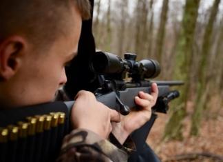A West Virginia hunter sights his gun.