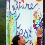 A festival-goer paints a community art board at the annual Culturefest festival at Pipestem, West Virginia.