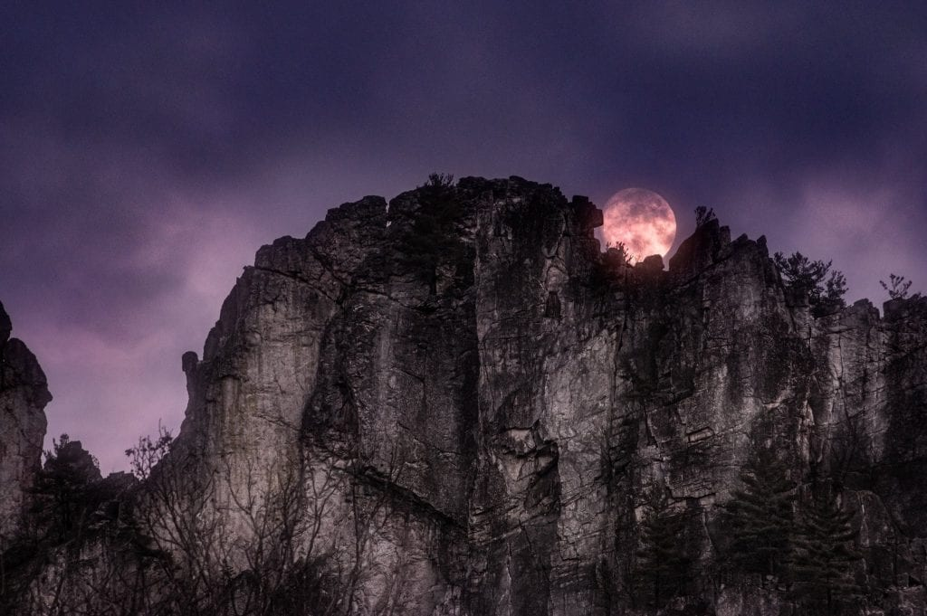 A full moon peeks over the towering blade of Seneca Rocks.