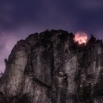 A full moon peeks over the towering blade of Seneca Rocks.