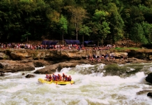 Rafters outfitted with River Expeditions watch raft-load plow through Sweets Falls on the Gauley River.