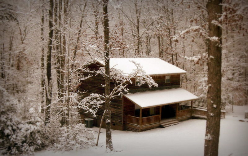 A cabin at River Expeditions awaits guests beneath a blanket of new-fallen snow.