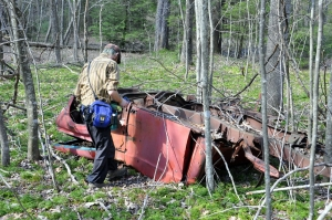 Justyn Marchese examines the remains of a vehicle abandoned in a remote farmstead area on the Polls Plateau Trail.