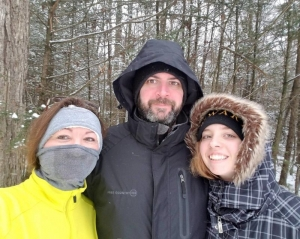 Active-living mentor Levi Moore poses with wife on daughter during a winter hike.