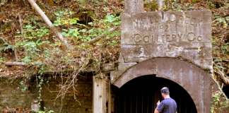 A gated mine opening along a rail trail near Ansted, West Virginia, attracts an interested hiker.