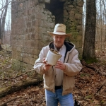Reporter David Sibray examines a kettle left near a ruin at little-known ghost town of Dun Glen.