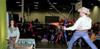 Frank Addington, Jr., takes aim at aspirin at the W.Va. Hunting and Fishing Show.