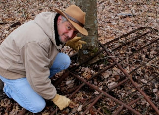 David Sibray examines an old bedstead left near a ruined farm while he hunts for evidence of the Grey Flats Ghost.