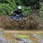 An ATV plows through a mudhole