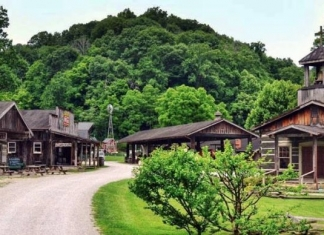 Log buildings collect along a gravel walk at the Heritage Farm Museum and Village near Huntington, West Virginia.