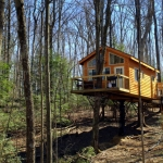 The Tuscany Treehouse looks out over the Meadow River woodlands at Country Road Cabins.