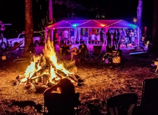 Festival-goers relax around a bonfire at Waynestock, celebrating its 20th year at River Expeditions.