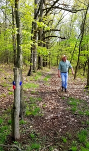 David Sibray follows a state boundary trail through the woods near the Reddick grave.