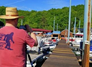 David Sibray sports a bigfoot souvenir t-shirt while photographing the Sutton Lake Marina.