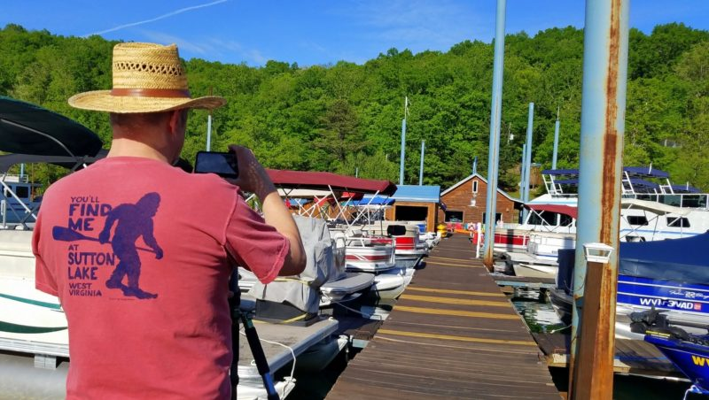 David Sibray sports a bigfoot souvenir t-shirt while photographing the Sutton Lake Marina.