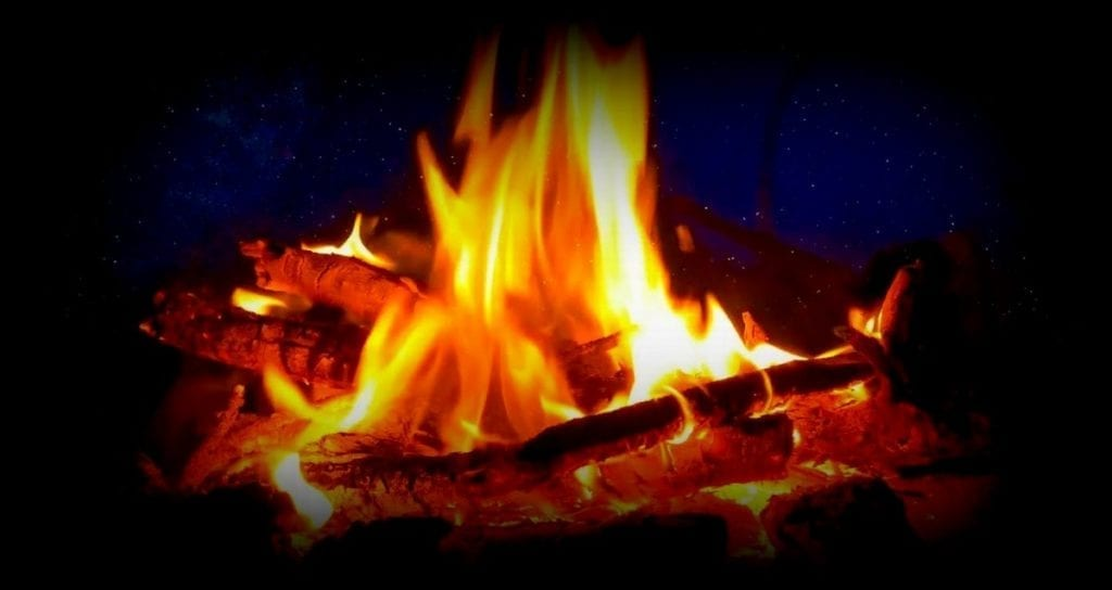 A campfire blazes in the West Virginia hills.