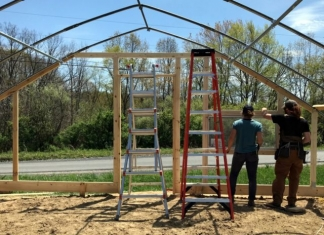 Susanna Wheeler and Brad Woolf raise a high tunnel to be used for the market garden.