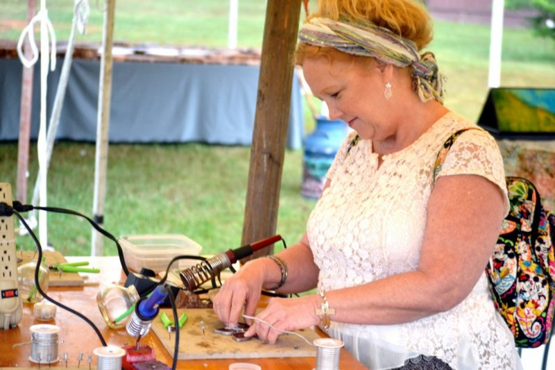 An artisan cuts stained glass at the Mountain State Art and Craft Fair at Ripley, West Virginia.
