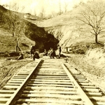 A vintage photo shows workers gathered outside the eastern portal of the Jenny Gap Tunnel.