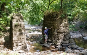 Justyn Marchese studies stone piers at the mouth of Lick Creek near the New RIver.