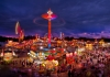 The midway at the State Fair of West Virginia rages with color at dusk at Fairlea, West Virginia.