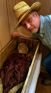 David Sibray inspects the larger of the tow Philippi Mummies on display in the museum.