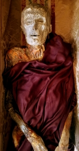 The larger mummy lies lifeless in a coffin.