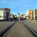 David Sibray stands warily between the rails that course through the center of Second Street in Saint Marys, West Virginia.