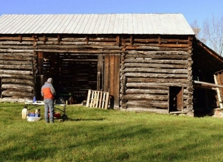 A researcher prepares to collect tree-ring samples from The Pitsenbarger Barn in Pendleton County.