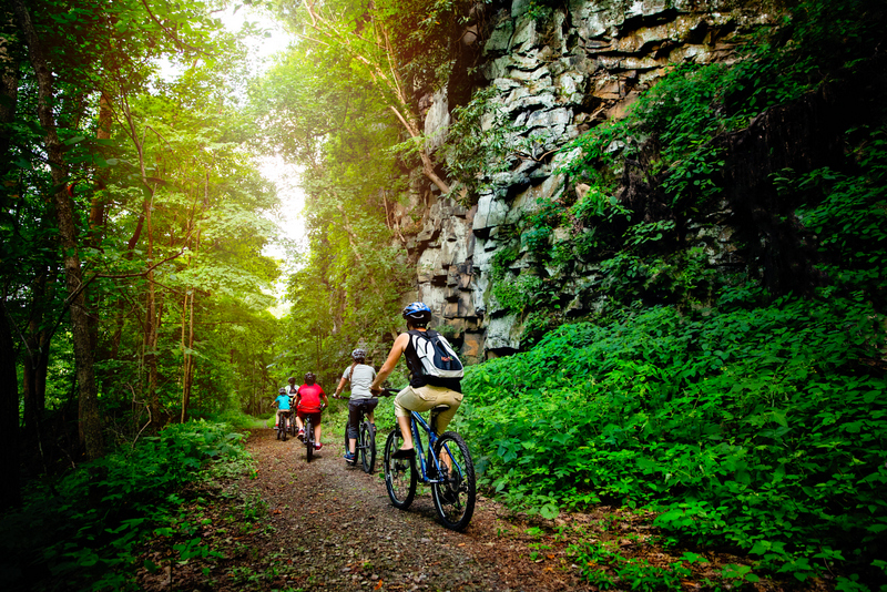 A family bikes a park trail in the New River Gorge National River.
