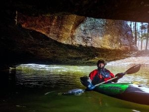A kayaker paddles into a cave along Paint Creek.