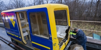 A maintenance worker inspects a wrecked PRT at West Virginia University.