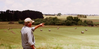 A farmer surveys pasture and cropland in eastern West Virginia.