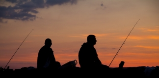 Anglers watch the sun set on a West Virginia lake.