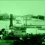 The Nina Paden docks at Belpre, Ohio. Parkersburg, with its tall courthouse tower, lines the Ohio River in the background.