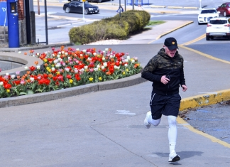 A jogger runs past the Chambers College of Business and Economics during the coronavirus outbreak.