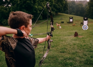 A West Virginia youth practices target shooting with bow and arrow. (Photo courtesy W.Va. Dept. of Commerce)