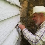Jim Costa examines clapboard siding for signs of period construction methods.