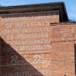 A faded sign graces the Tomchin Furniture and Coca-Cola Bottling Works building.
