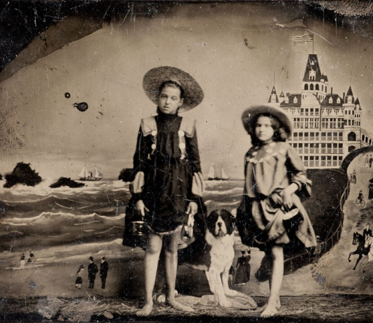 Two young girls pose for a vintage tintype portrait.